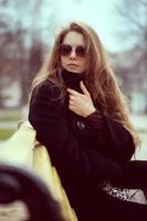 mujer elegante, en, gafas de sol, en el banquillo foto