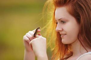 Girl holds brown caterpillar on her hand photo
