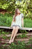 niña en un vestido de verano sentada y relajándose foto