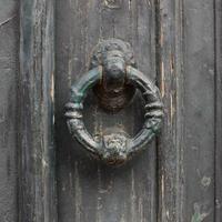 Tirador de puerta vieja en la puerta de madera verde foto