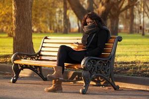 Young sad woman sitting alone photo