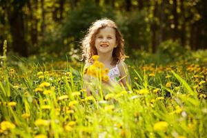 niña con un ramo de dientes de león foto
