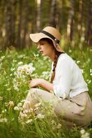 Linda mujer arranca margaritas en un prado foto
