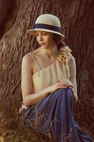 mujer joven, en, retro, sombrero, se sentar sobre la hierba foto