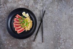 Trozos de atún frito con kenoa y frijoles en un plato foto