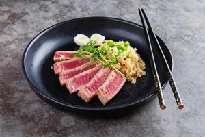 Black plate with quinoa and fried tuna slices photo
