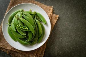 guisantes verdes dulces frescos en un plato foto