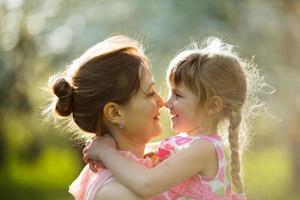 feliz joven madre sostiene a una hija foto