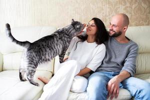 hombre y mujer joven con su gato en el sofá en casa foto