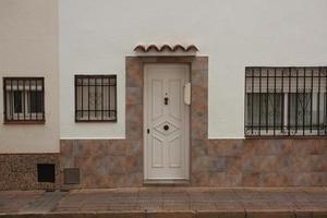 Puerta de madera en una casa de estuco blanco foto