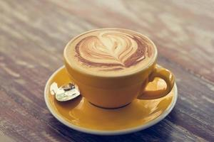 Coffee cup on wooden background, Vintage color tone photo