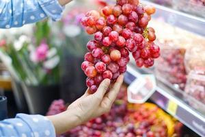 Mujer eligiendo racimo de uva roja fresca para comprar en el supermercado foto