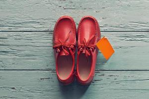 Male shoes with tag on wooden background photo