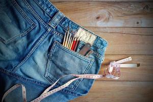 Jeans with measure and crayons, paintbrushs in back pocket on wooden photo