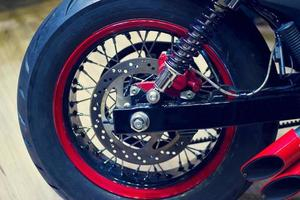 Red motorcycle back wheel on wooden background photo