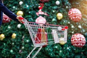 Woman shopper with bags in shopping cart on holidays photo