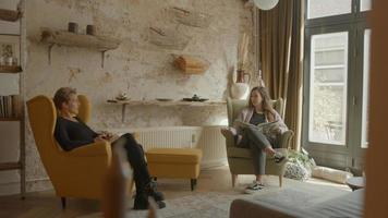 Two women casually talking sitting in living room photo