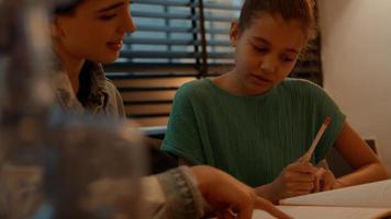 Woman helping girl doing homework at table photo
