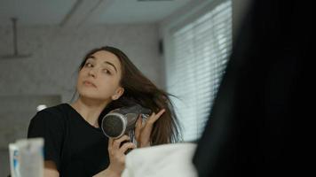 Woman using hairdryer in bathroom looking in mirror photo