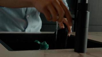 Man wringing cloth at sink photo