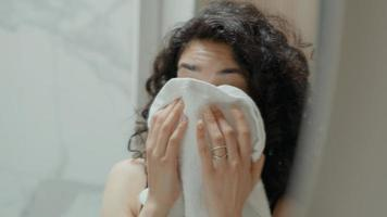 Woman in bathroom looks in mirror wiping face and adjusting hair photo