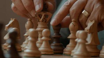 Hands of man moving and removing chess pieces on chessboard photo