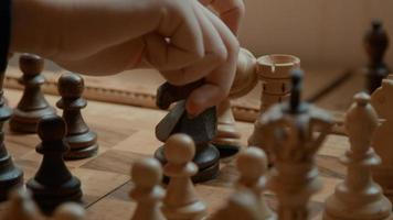 Hand of girl moving and removing chess pieces on chessboard photo