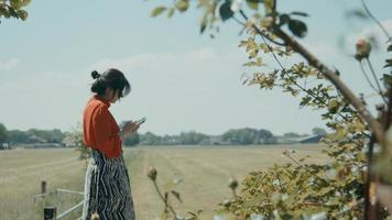 Woman standing in field scrolling on smartphone photo