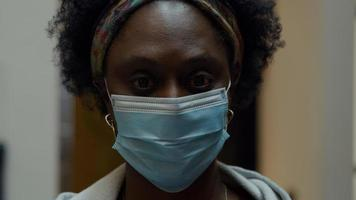 Cerca de negro mujer madura con mascarilla foto