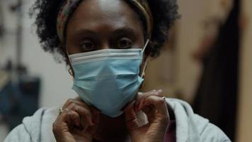Head shot of black mature woman smiling putting on face mask photo