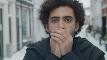 Cerca del hombre de Oriente Medio soplando aire caliente en las manos foto