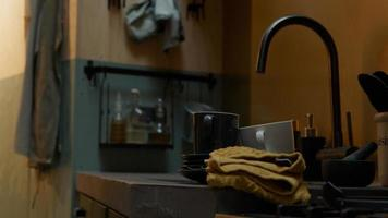 Close up of sink and part of counter with tap, cups photo