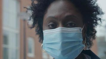 Close up of black mature woman standing outside, wearing face mask photo