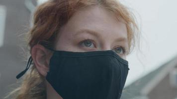 Close up of young white woman standing outside, wearing face mask photo