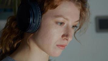 joven mujer blanca en auriculares, la luz de la pantalla se refleja en los ojos foto
