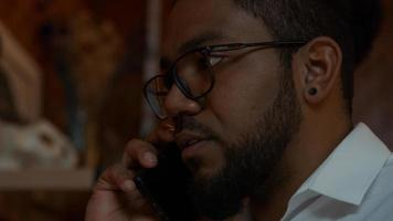 Close up of black man wearing glasses, mobile phone on ear, talking photo