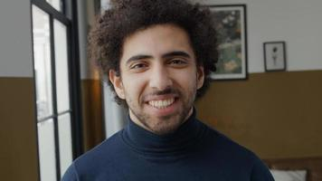 Close up of young Middle Eastern man looking into camera, laughing photo