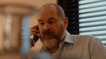 Man at table talking on smartphone photo