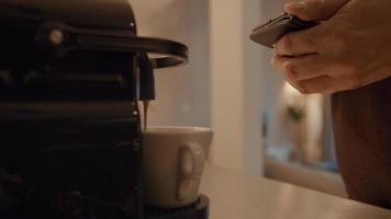 La mano del hombre que sostiene el teléfono inteligente y el café se queda sin máquina foto