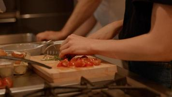 Woman preparing meal whilst talking with man in kitchen photo