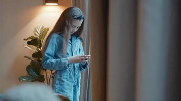 Girl standing typing on smartphone in front of window photo