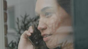 Young mixed race woman calling whilst looking through window photo