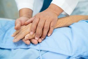 Doctor holding hands Asian senior woman patient with love photo