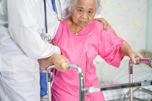 Asian  doctor care, help and support senior patient walk with walker photo