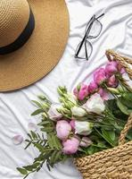 Straw hat and  bouquet of pink rose flowers on white background photo