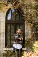 Pretty young woman standing with mobile phone on street at autumn day photo