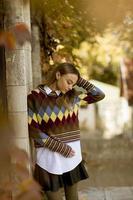Mujer joven de pie afuera en el soleado día de otoño foto