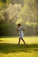 Cute little girl having fun under irrigation sprinkler photo