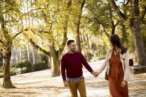 Young woman and man walking in city park holding hands photo