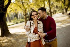 Mujer joven y hombre caminando en el parque de la ciudad tomados de la mano foto